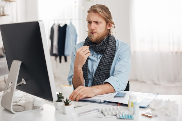 Sick ill bearded man sits in front of computer, tries to concentrate on work, holds spectacles in hand. exahausted office worker tired, has sedentary lifestyle, isolated against office background.