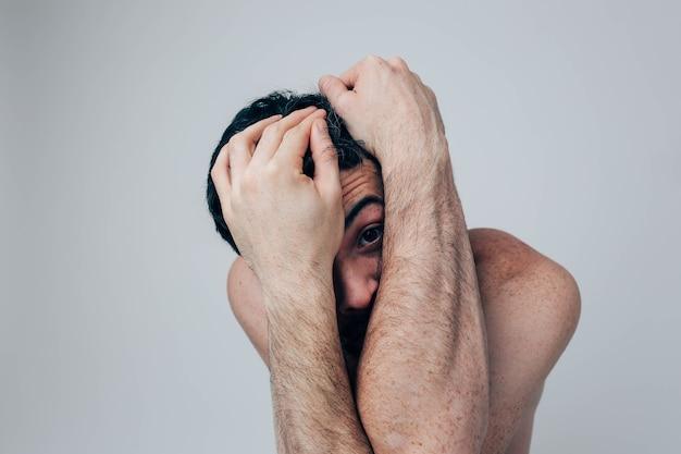 Больной больной сумасшедший парень смотрит прямо сквозь руки. накройте ими лицо. беспорядок и депрессия. запутанный и сумасшедший.