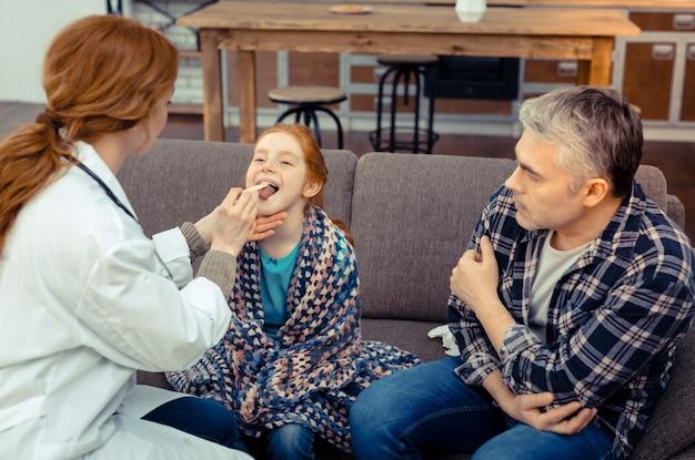 아픈 아이. 그녀의 목을 확인하는 동안 의사 앞에 앉아 귀여운 빨간 머리 소녀