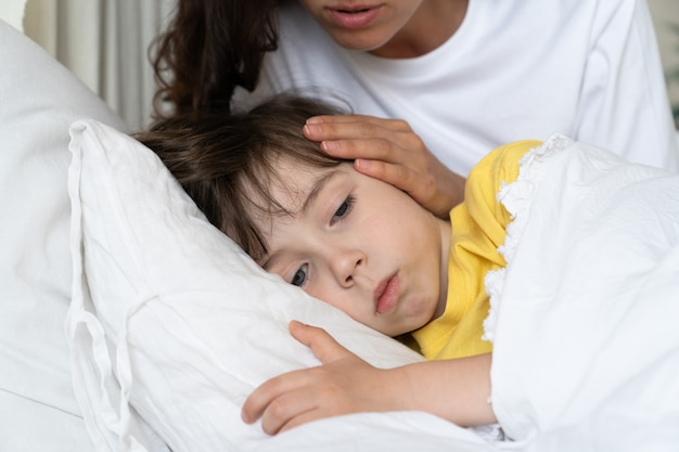Sick kid lying in bed with worried mom comforting boy suffering from fever or flu home cure concept