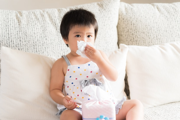 Sick little asian girl wiping or cleaning nose with tissue sitting on sofa at home