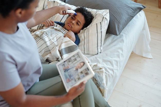 ベッドに横になっていて、タブレットを持った注意深い母親がオンライン医療ビデオを見て体温を測定している病気の少年