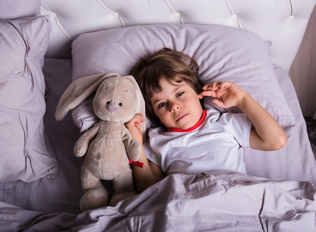 A sick little boy in pajamas is lying in bed with a soft toy