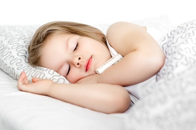 Sick little child girl lying in bed with thermometer