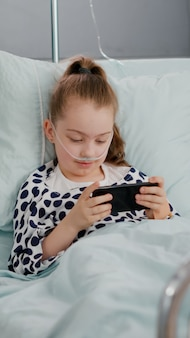 Piccolo bambino malato che riposa a letto giocando ai videogiochi online utilizzando lo smartphone