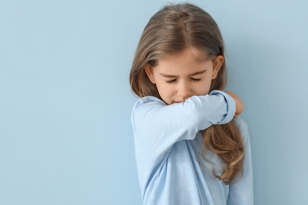 色の壁に病気の少女