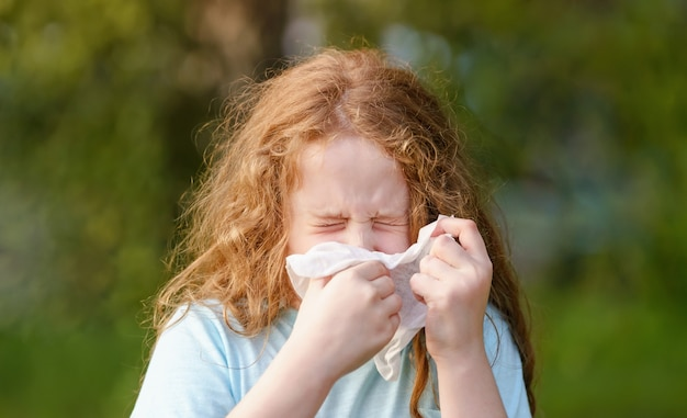 Sick little girl sneeze in handkerchief on outdoors.