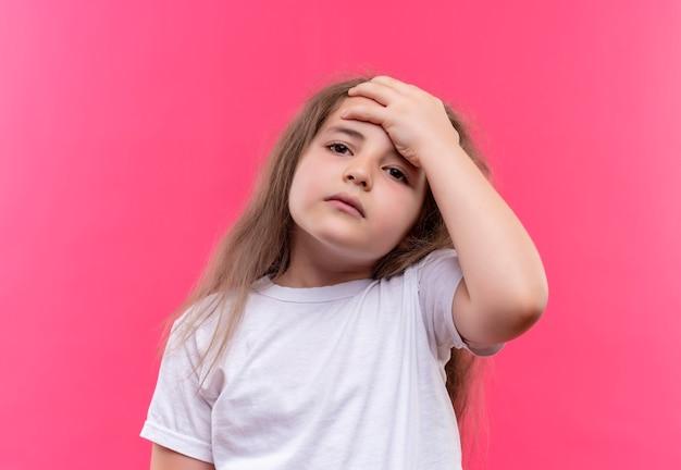 흰색 티셔츠를 입고 아픈 어린 학교 소녀 격리 된 분홍색 배경에 이마에 그녀의 손을 넣어