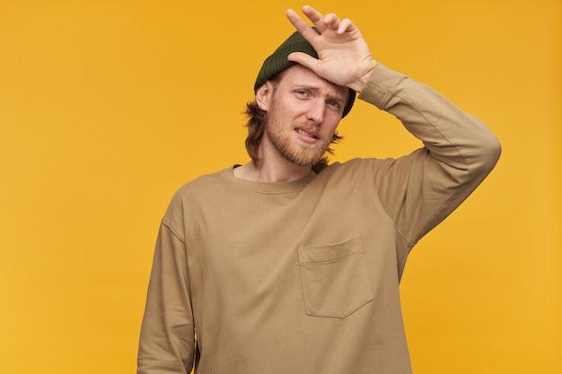 Больного вида мужчина, усталый бородатый парень со светлыми волосами. в зеленой шапке и бежевом свитере. касание рукой лба. изолированные над желтой стеной