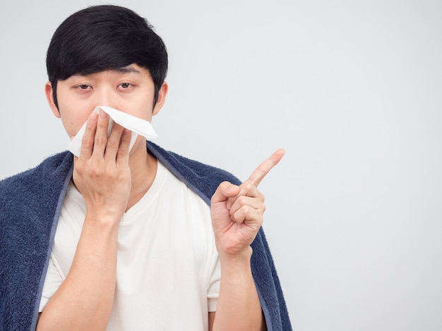 아픈 아시아인은 공간 흰색 배경에서 조직 포인트 손가락으로 코를 닫습니다.
