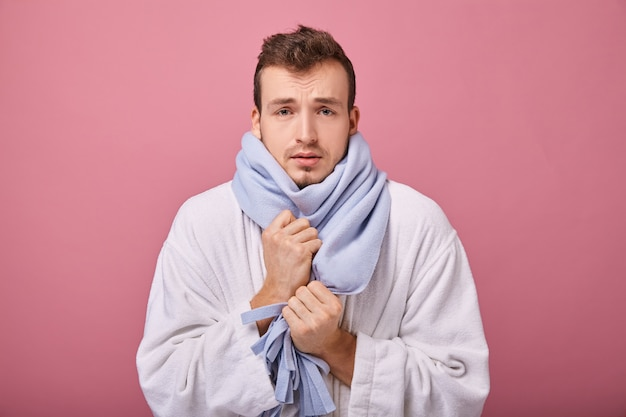 Sick man in blue scarf and snow-white coat with look of patient is frozen and trembling