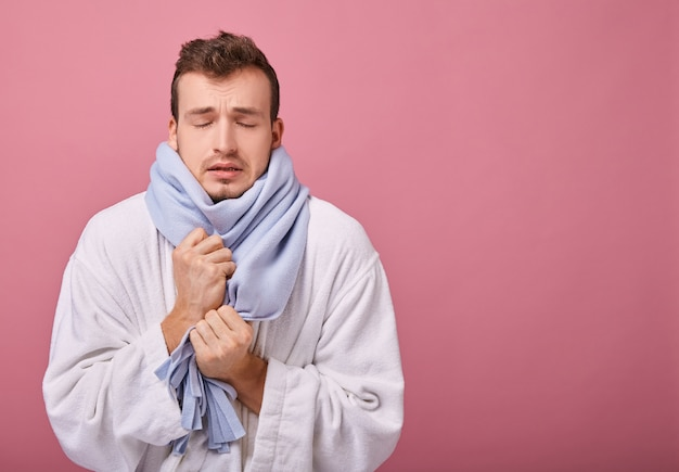Sick man in blue scarf and white bathrobe is frozen and trembling