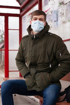 Sick man in a bus station, protected against the chinese virus in public places.