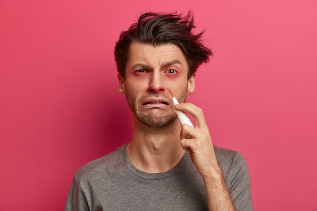 Sick man caught cold, suffers from rhinitis or blocked nose, uses nasal spray, has red swollen eyes, recommends medical treatment, wants to recover quickly, isolated on pink wall. health care concept