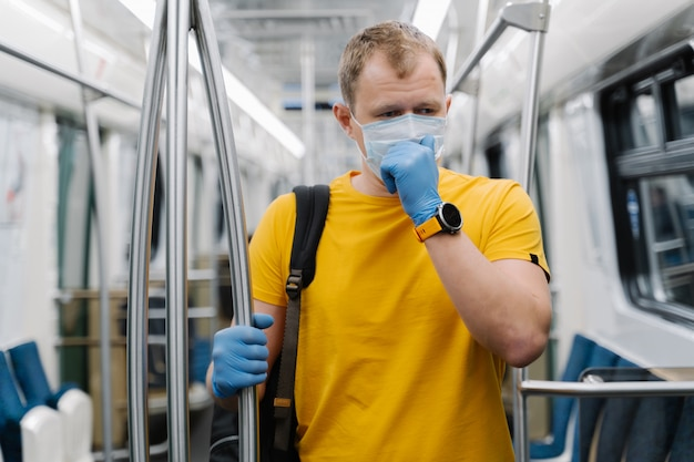 Sick man coughs, wears medical mask and protective rubber gloves, commutes to work in metro carriage