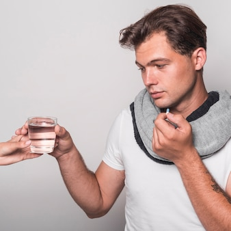 Sick man holding glass of water from person's hand taking capsule