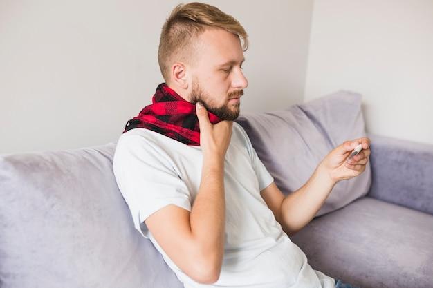 Больной человек держит руку на шее