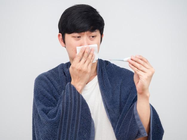 코에 티슈를 대고 손에 온도계를 보고 있는 아픈 남자