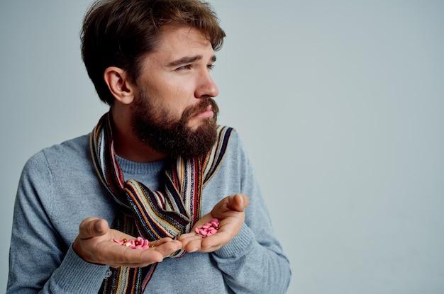 손에 약을 들고 스웨터를 입은 아픈 남자 건강 문제 밝은 배경. 고품질 사진