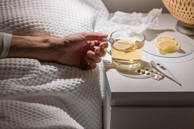 Больной человек в постели держит чашку горячего чая с лимоном, пьет горячий напиток, чтобы выздороветь от гриппа, лихорадки и вирусов.
