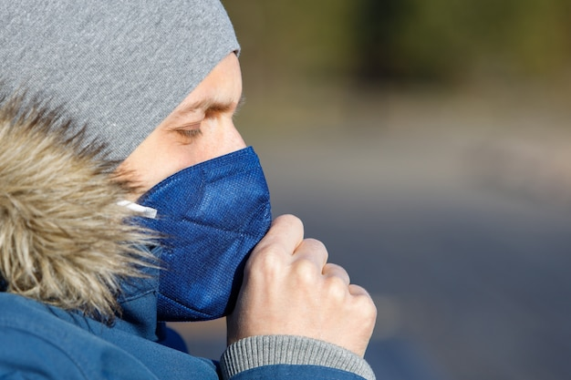 Больной человек в синей куртке с капюшоном, имеющий простуду, кашель и носить медицинскую маску