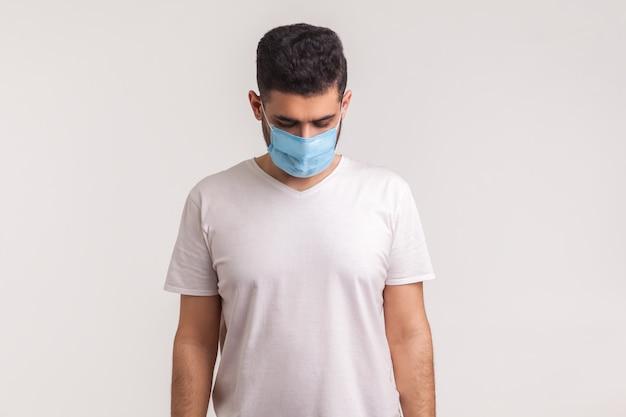 コロナウイルス感染について悲しげに、怖がって、必死に見下ろしている衛生マスクの病人
