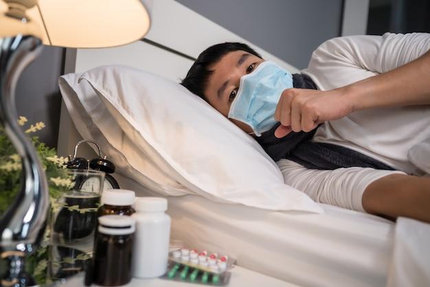 Больной человек в медицинской маске кашляет и страдает от вирусной болезни и лихорадки в постели, концепция пандемии коронавируса.