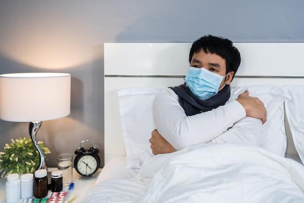 寒さを感じてベッドでウイルス病や発熱、コロナウイルスのパンデミックの概念に苦しんでいる医療用マスクの病人。