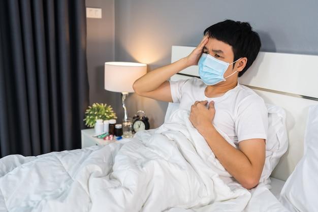 医療用マスクの病人は頭痛とウイルス病とベッドでの発熱、コロナウイルスのパンデミックの概念に苦しんでいます。