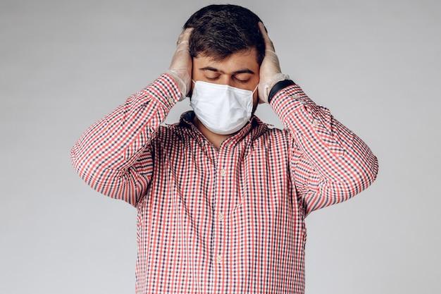 Больной в медицинской маске на лице и в защитных перчатках на руках чувствует головную боль