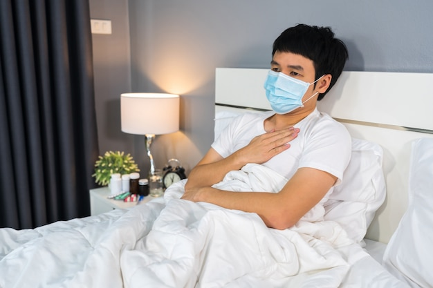 Больной человек в медицинской маске страдая от вирусной болезни и лихорадки в кровати, концепции пандемии коронавируса.