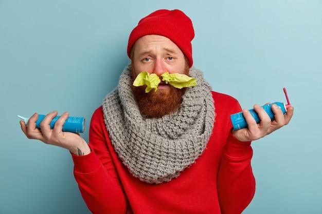 鼻にティッシュペーパーと喉の痛みのためのスプレーで暖かい服を着た病人
