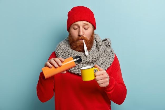 온도계와 컵 따뜻한 옷에 아픈 사람