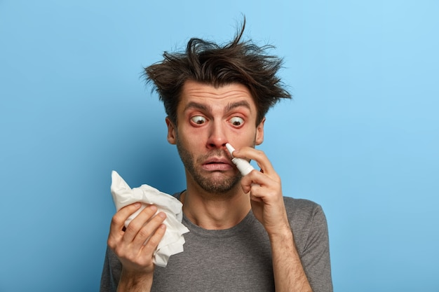 Sick man injects nasal drop for blocked nose, suffers from cold, allergy or rhinits, rubs with handkerchief, feels unwell, has bugged eyes, isolated on blue wall stays at home during course of disease