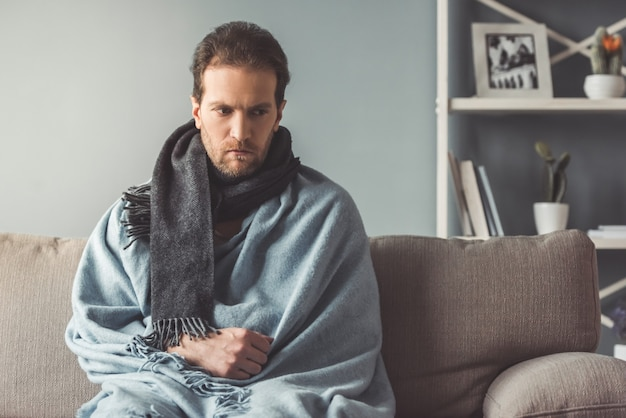 Sick man is looking sadly down while sitting on couch