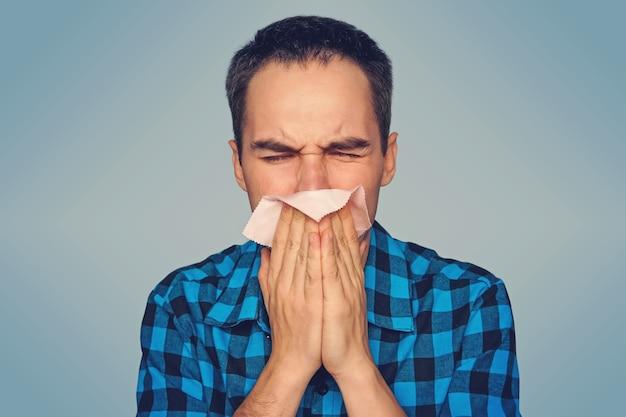 孤立した病人は鼻水が出ています。若い男が青い背景にピンクのスカーフでくしゃみをします。秋の風邪。