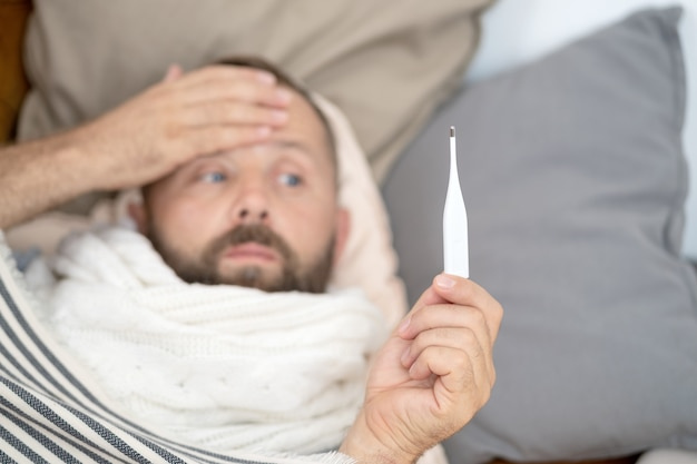 Sick man lying on sofa checking his temperature at home in the living room