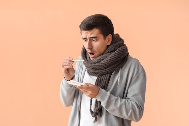 Sick man measuring temperature on color surface