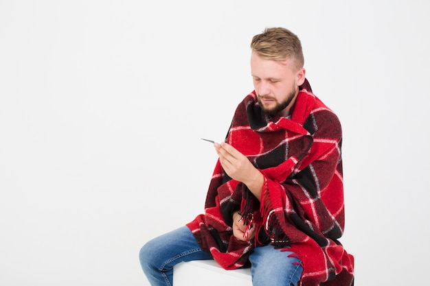 Sick man measuring temperature