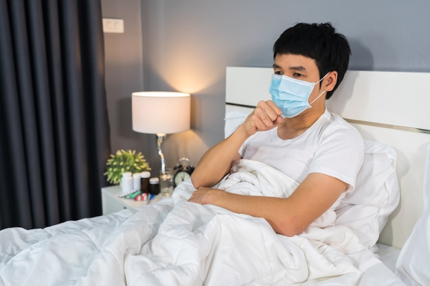 Sick man in medical mask coughing and suffering from virus disease and fever in bed, coronavirus pandemic concept.