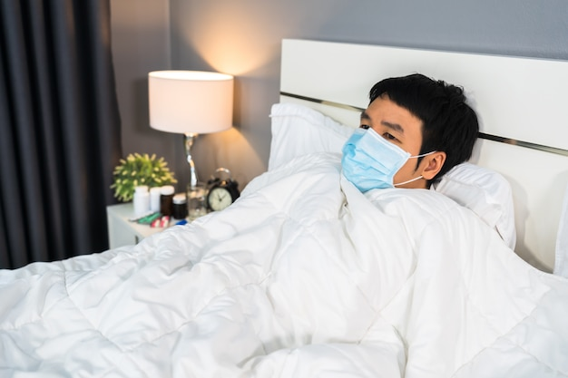 Sick man in medical mask feeling cold and suffering from virus disease and fever in bed, coronavirus pandemic concept.