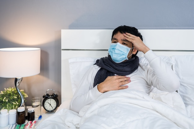 Sick man in medical mask is headache and suffering from virus disease and fever in bed, coronavirus pandemic concept.