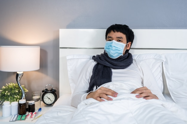 Sick man in medical mask suffering from virus disease and fever in bed, coronavirus pandemic concept.