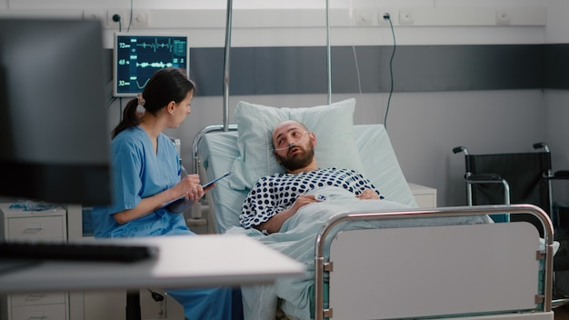 Sick man sitting in bed with oxygen tube explaining sickness symptom to medical nurse