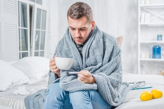 Sick man sitting on bed holding cup of coffee checking the fever in thermometer