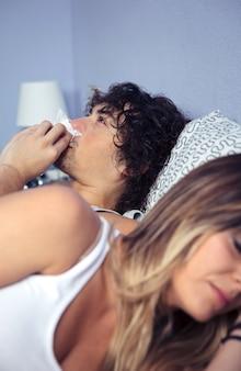 病人がくしゃみをして、寝ている若い女性にベッドサイドに横たわっているティッシュで鼻を覆っている。病気とヘルスケアの概念。