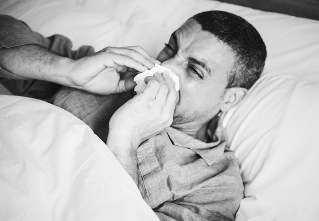 Sick man sneezing in bed