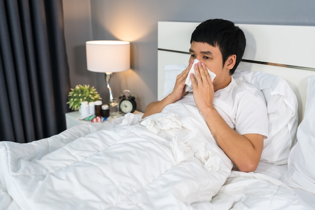 Sick man sneezing into tissue lying in bed