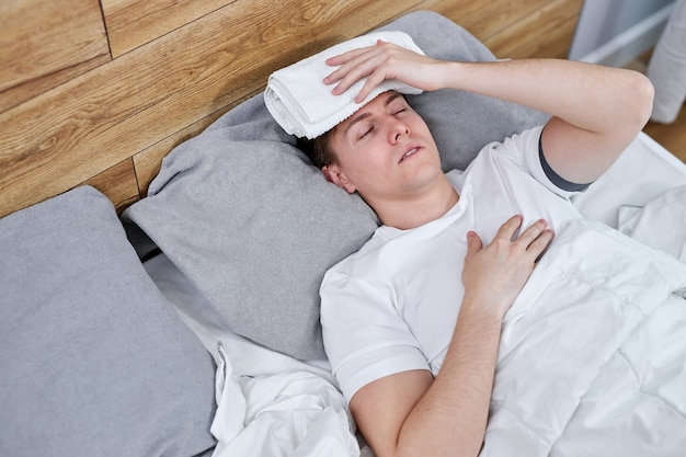Sick man suffering from covid-19 symptoms lying on bed at home, high fever prevent him from living a normal life, he has to be on self-isolation