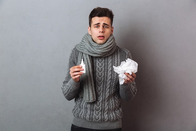 Sick man in sweater and scarf holding serviette and spray while looking